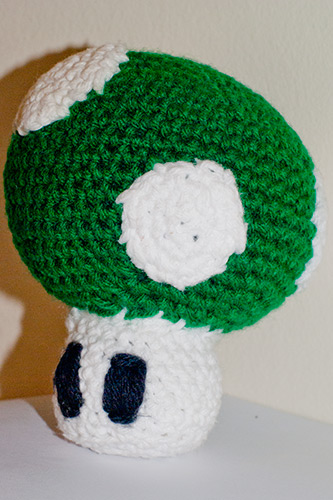 A crochet figure of a 1-up mushroom.
