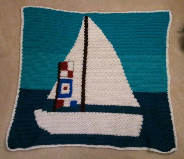 A crocheted baby blanket with an image of a sailboat.